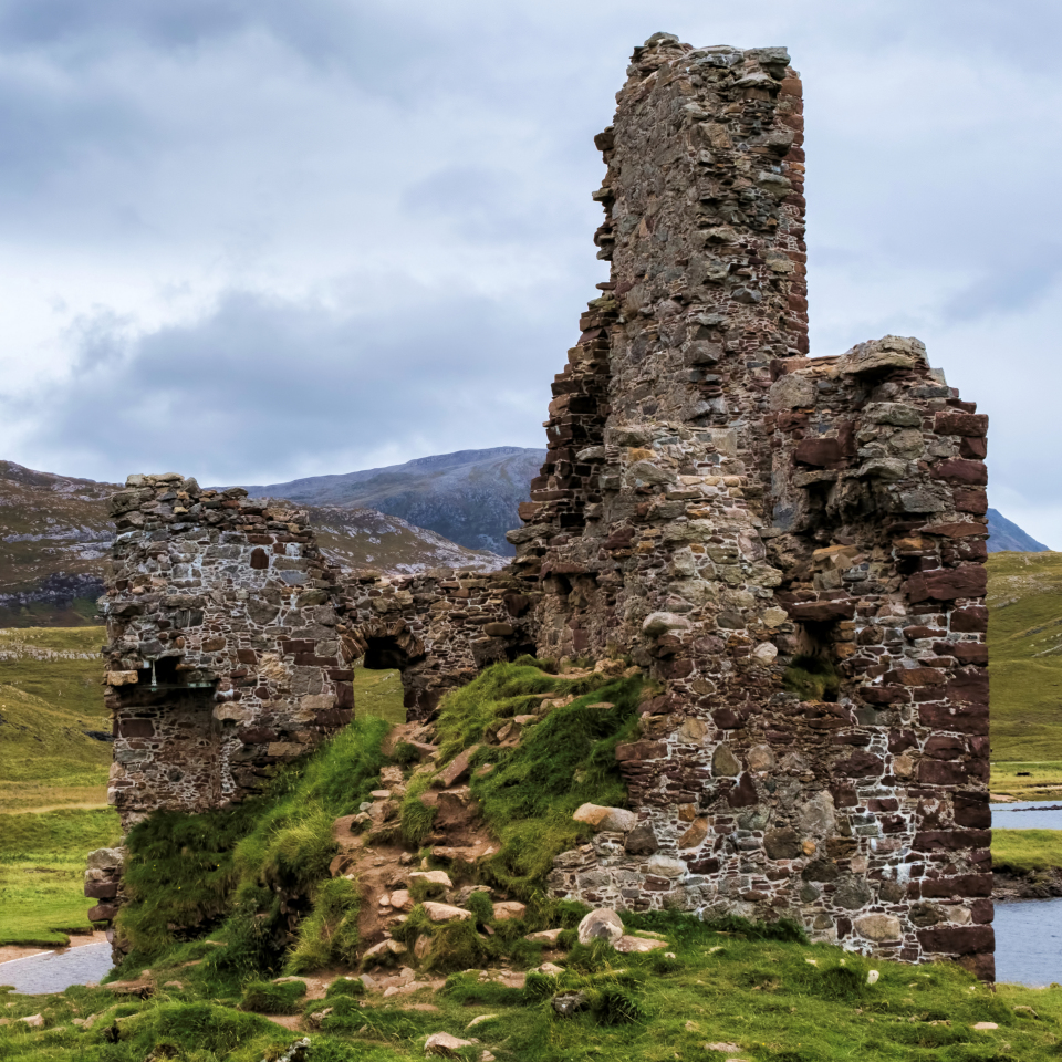 The ruins of Ardvreck Castle against the Highland hills.